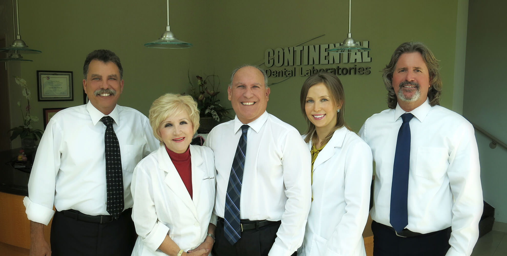 Our Continental Dental Lab Team showing and standing side by side in front of our logo in the office