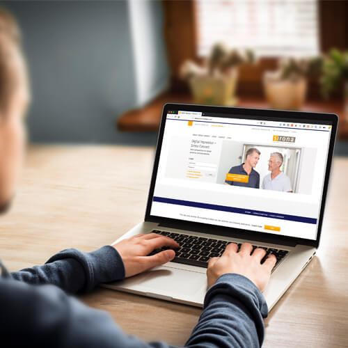 Man on a laptop visiting Sirona Cerec-connect website