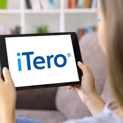 Woman holding a tablet with iTero logo on it